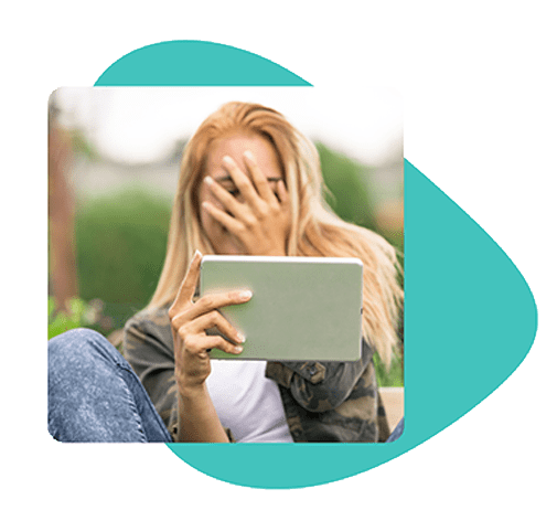 Girl suffering from acne covering face whilst browsing tablet